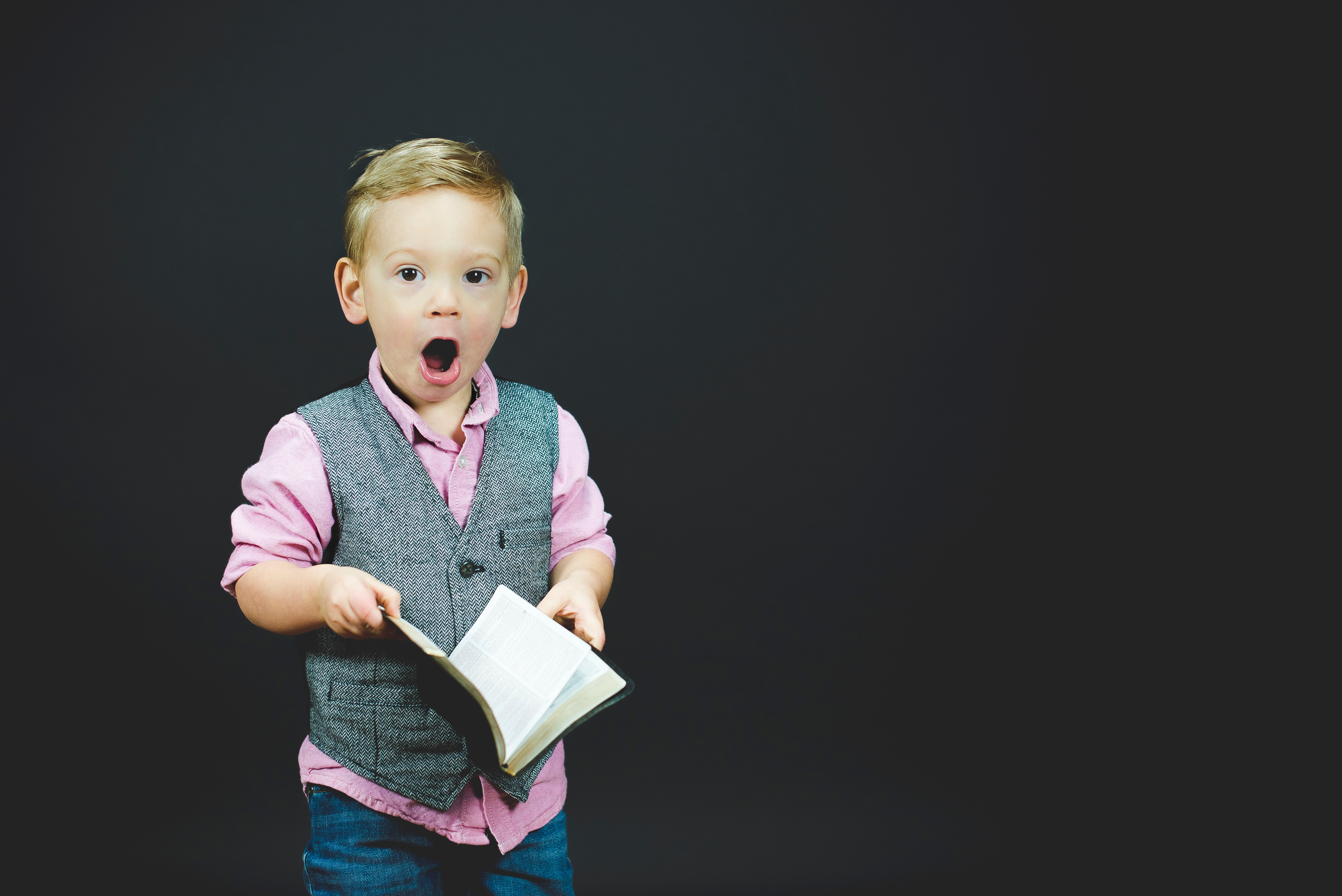 little boy with book and surprised expression
